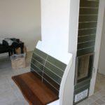 Moderner Säulen-Kachelofen mit wärmender Sitzbank